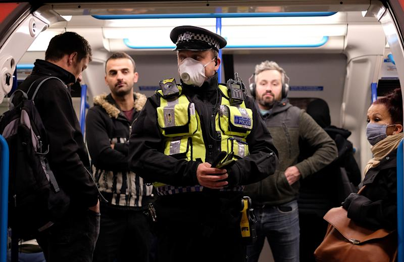 A police officer wearing PPE (personal protective equipment), including a face mask as a precautionary measure against COVID-19, stands with commuters as they travel in the morning rush hour on TfL (Transport for London) London underground Victoria Line trains from Finsbury Park towards central London on May 13, 2020, as people start to return to work after COVID-19 lockdown restrictions were eased. - Britain's economy shrank two percent in the first three months of the year, rocked by the fallout from the coronavirus pandemic, official data showed Wednesday, with analysts predicting even worse to come. Prime Minister Boris Johnson began this week to relax some of lockdown measures in order to help the economy, despite the rising death toll, but he has also stressed that great caution is needed. (Photo by Isabel INFANTES / AFP) (Photo by ISABEL INFANTES/AFP via Getty Images)
