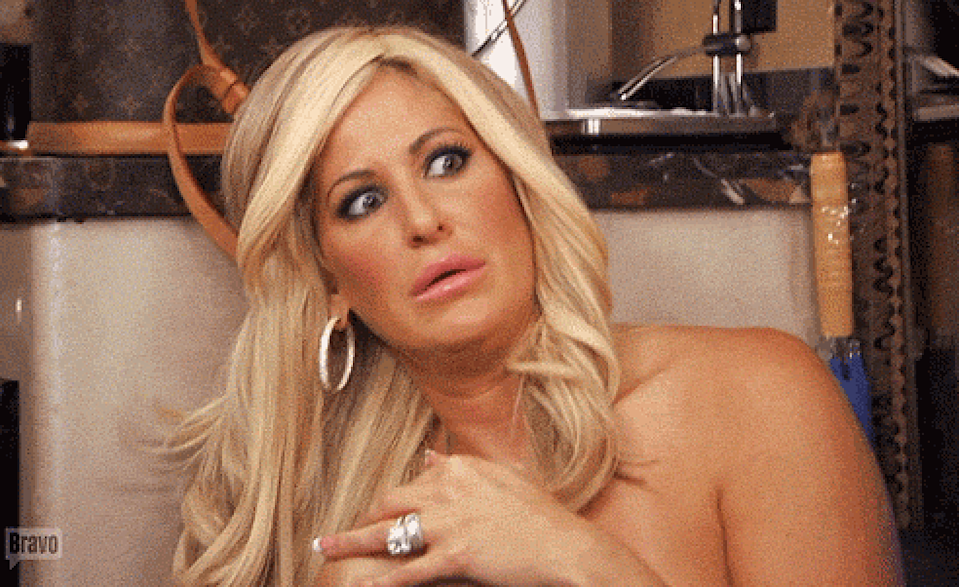 One of the Real Housewives holding her hand over her chest in shock and awe