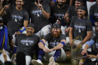 FILE - In this Tuesday, Oct. 27, 2020, file photo, Los Angeles Dodgers manager Dave Roberts, left foreground, sits beside third baseman Justin Turner as they pose for a group picture after the Dodgers defeated the Tampa Bay Rays 3-1 in Game 6 to win the baseball World Series in Arlington, Texas. Baseball nearly made it through its version of playoff bubbles unscathed; two innings before the World Series ended, Justin Turner of the now-champion Los Angeles Dodgers Turner was pulled from the game after MLB was notified that he had tested positive for COVID-19. (AP Photo/Eric Gay, File)