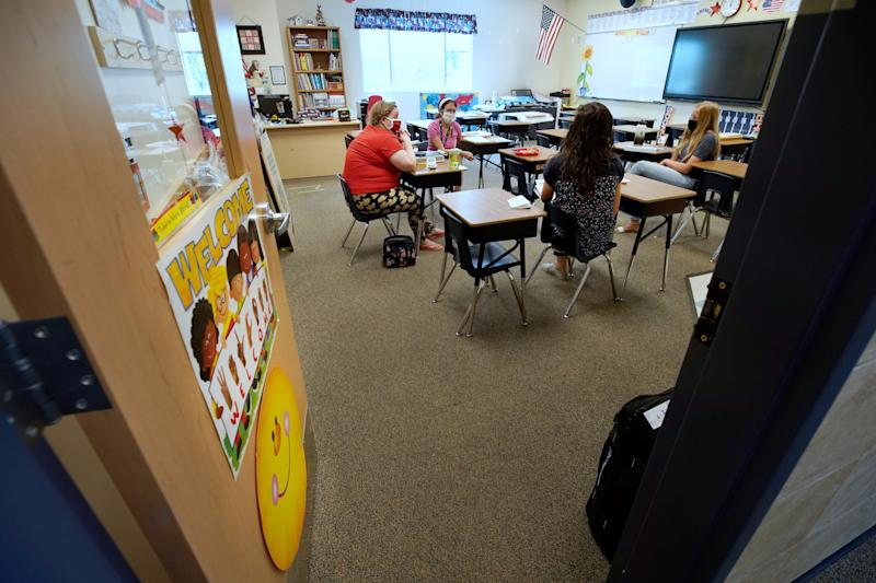 PROVO, UT - AUGUST 05: Second grade teachers wearing masks meet at Freedom Preparatory Academy as they begin to prepare to restart school after it was closed in March due to COVID-19 on August 5, 2020 in Provo, Utah. The school is planning to have students return on August 18 for five days a week instruction, but with reduced hours during the day. (Photo by George Frey/Getty Images)