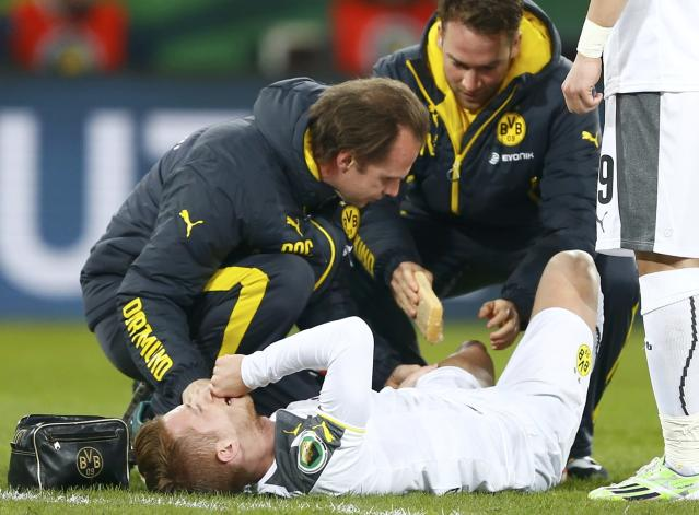 Borussia Dortmund's Marco Reus receives medical help after being injured in his team's German Cup (DFB Pokal) soccer match against Dynamo Dresden in Dresden March 3, 2015. REUTERS/Hannibal Hanschke (GERMANY - Tags: SOCCER SPORT) DFB RULES PROHIBIT USE IN MMS SERVICES VIA HANDHELD DEVICES UNTIL TWO HOURS AFTER A MATCH AND ANY USAGE ON INTERNET OR ONLINE MEDIA SIMULATING VIDEO FOOTAGE DURING THE MATCH.
