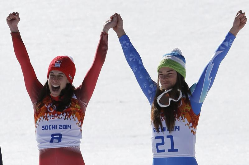 Women's downhill gold medalists Switzerland's Dominique Gisin, left, and Slovenia's Tina Maze, right, hold hands during a flower ceremony at the Sochi 2014 Winter Olympics, Wednesday, Feb. 12, 2014, in Krasnaya Polyana, Russia. (AP Photo/Christophe Ena)