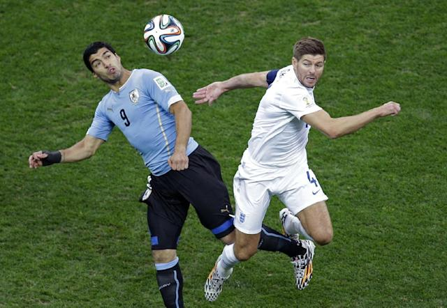 Uruguay's Luis Suarez, left, and England's Steven Gerrard challenge for the ball during the group D World Cup soccer match between Uruguay and England at the Itaquerao Stadium in Sao Paulo, Brazil, Thursday, June 19, 2014. (AP Photo/Michael Sohn)