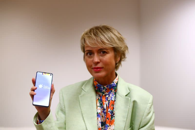 Artigas, head of Spain's state digital and artificial intelligence unit, poses holding a mobile phone with the Radar Covid app in Madrid