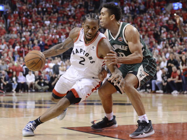 Toronto Raptors forward Kawhi Leonard (2) drives to the net around Milwaukee Bucks guard Malcolm Brogdon (13) during the second overtime period of Game 3 of the NBA basketball playoffs Eastern Conference finals in Toronto on Sunday, May 19, 2019. (Nathan Denette/The Canadian Press via AP)