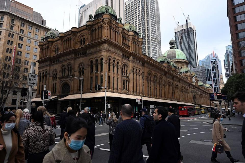 Pedestrians, some wearing face masks, walk through Sydney's central business district on August 12, 2020. (Photo by SAEED KHAN/AFP via Getty Images)
