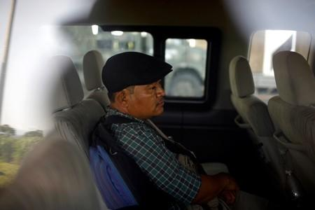 A migrant from Guatemala waits inside a van after he was detained at a checkpoint on a road in Tuxtla Chico