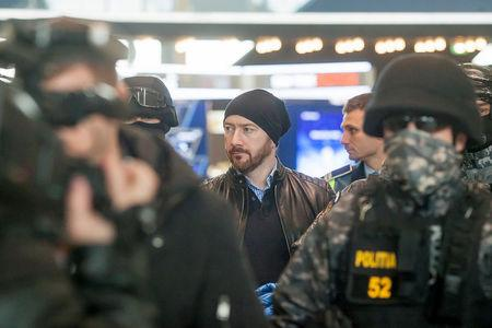 Chilean economist Garay is escorted by law enforcement officers as he is extradited from Romania to Chile