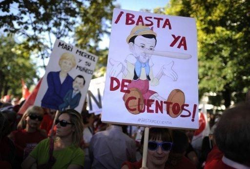 """A protester holds a banner depecting Spanish PM Mariano Rajoy dressed as pinocchio reading """"Enough lies"""" during a demonstration against government austerity measures aimed at slashing the public deficit. A sea of chanting protesters from across Spain have gathered in Madrid for a rally against government austerity measures aimed at avoiding the need for a financial bailout"""