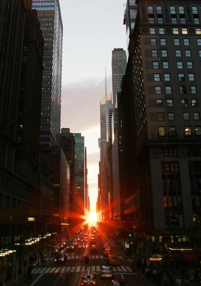 """The sun is seen as it sets between Manhattan buildings on 42nd Street during a phenomenon known as """"Manhattanhenge,"""" Wednesday, July 13, 2011 in New York City. Manhattanhenge, sometimes referred to as the Manhattan Solstice, happens when the setting sun aligns with the east-to-west streets of the main street grid. The term comes from Stonehenge, at which the sun aligns with the stones on the solstices in England. (AP Photo/Julio Cortez)"""