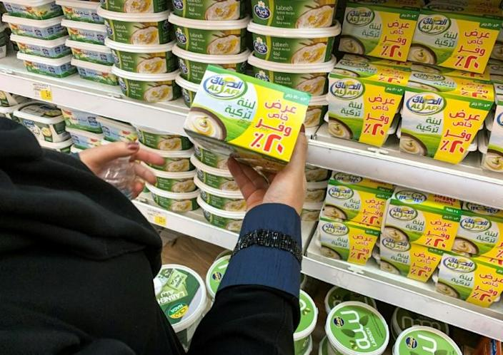 A woman holds a pack of Turkish labneh (strained yogurt) while shopping at a supermarket in Riyadh on October 18