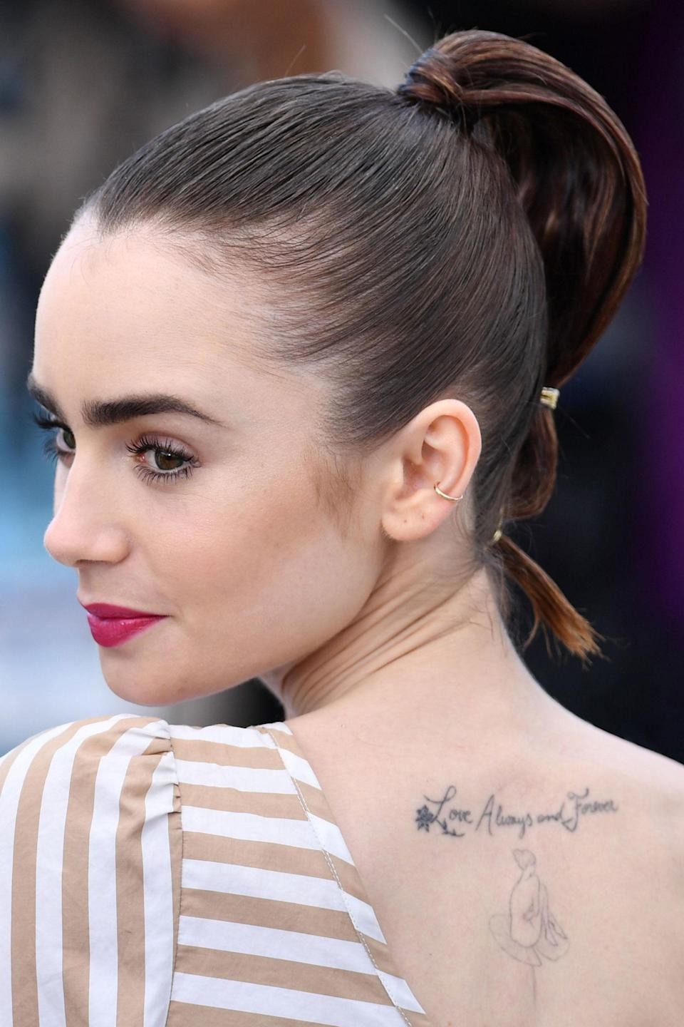 <p>At the photocall for <em>Okja</em>, Collins wore a slick ponytail with glamorous gold accents and a hot pink lip.</p>