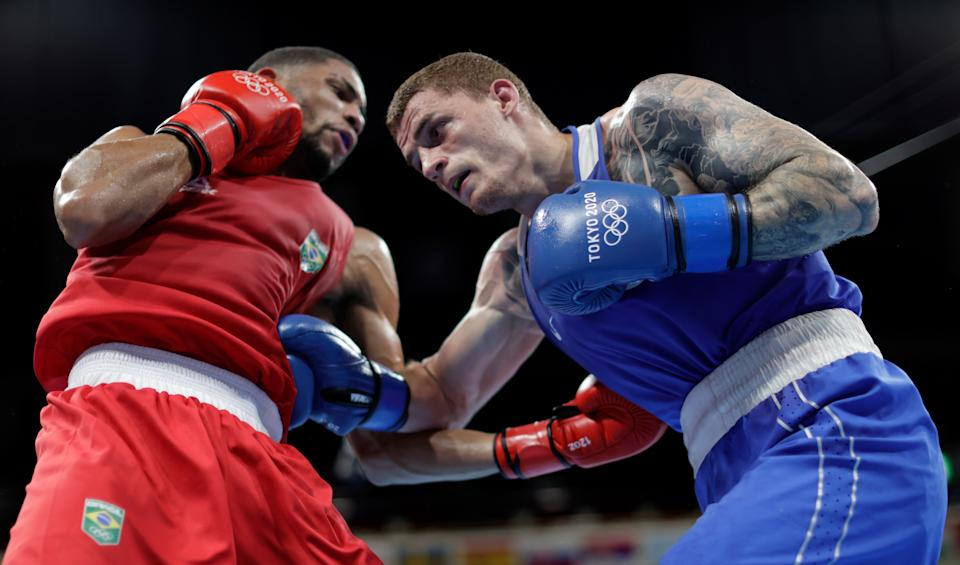 <p>Hebert Sousa (red) of Team Brazil exchanges punches with Gleb Bakshi of Team Russian Olympic Committee during the Men's Middle (69-75kg) semi final on day thirteen of the Tokyo 2020 Olympic Games at Kokugikan Arena on August 05, 2021 in Tokyo, Japan. (Photo by Ueslei Marcelino - Pool/Getty Images)</p>
