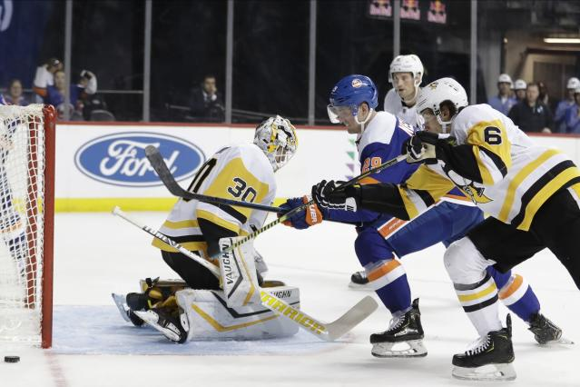Pittsburgh Penguins' John Marino (6) and New York Islanders' Brock Nelson (29) fights for control of the puck after goaltender Matt Murray (30) deflected a shot on goal during the second period of an NHL hockey game Thursday, Nov. 21, 2019, in New York. (AP Photo/Frank Franklin II)