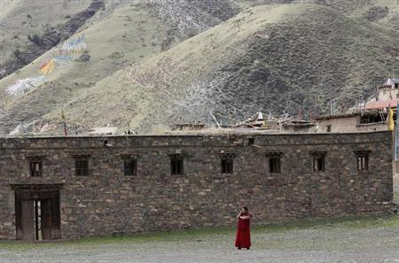 A Tibetan monk uses a mobile phone near the Dzamthang Jonang monastery in Barma township