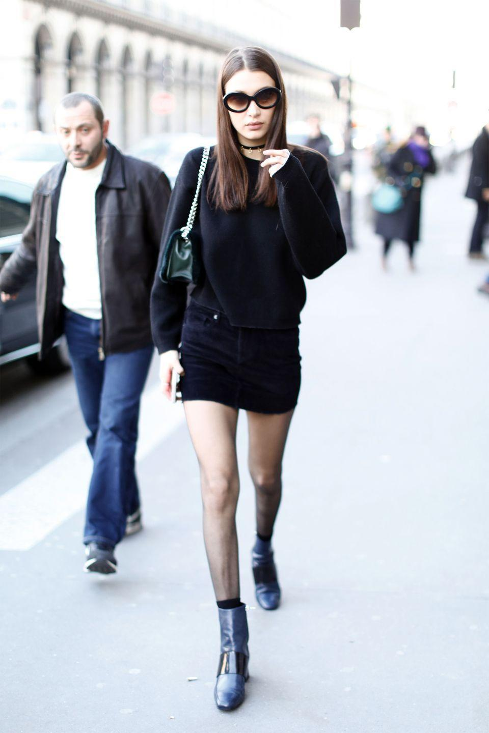 <p>In a black sweater, black mini skirt, ASKA leather boots, choker, rounded Sunday Somewhere sunglasses and olive green bag while out in Paris.</p>