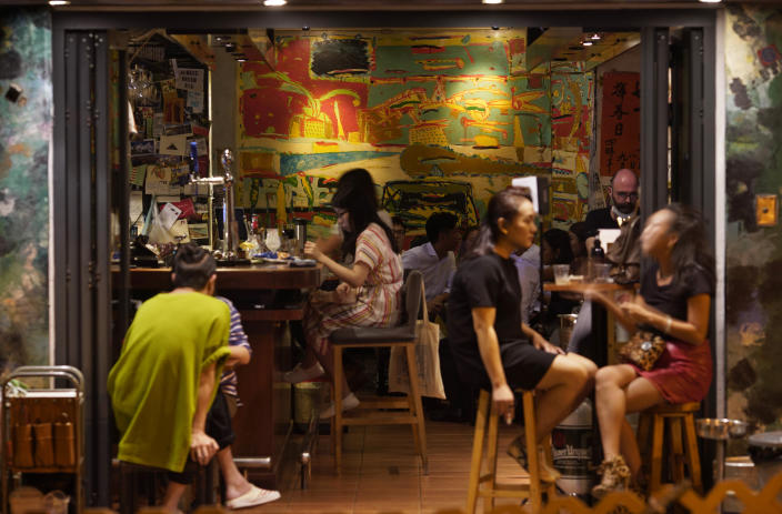 In this Oct. 7, 2020 photo, customers sit at Club 71 in Hong Kong. The bar known as a gathering place for pro-democracy activists and intellectuals is closing. For years, the storied bar has served as a watering hole for the city's pro-democracy activists and intellectuals, who could freely engage in discussions over a round of beer or two. (AP Photo/Vincent Yu)