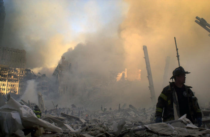 A firefighter moves through piles of debris at the site of the World Trade Center in New York, Tuesday, Sept. 11, 2001. (AP Photo/Graham Morrison)