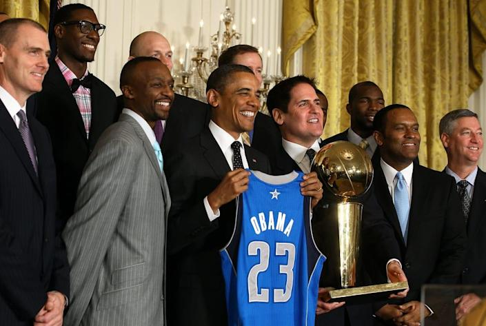 """<div class=""""inline-image__caption""""><p>President Barack Obama is flanked by owner Mark Cuban and members of the Dallas Mavericks during an event to honor the NBA champions in the East Room at the White House on January 9, 2012, in Washington, D.C.</p></div> <div class=""""inline-image__credit"""">Mark Wilson/Getty</div>"""