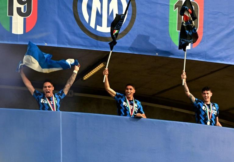(From L) Inter Milan's Lautaro Martinez, Achraf Hakimi and Alessandro Bastoni celebrate after lifting the Serie A title.