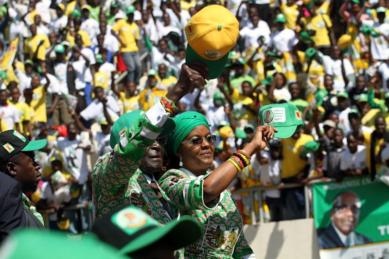 Zimbabwean President and Zanu PF leader President Robert Mugabe, left, and his wife Grace greet the crowd upon arrival at his last campaign rally in Harare, Sunday, July, 28, 2013. Mugabe is set to contest against his main rival Morgan Tsvangirai in an election set for July 31.(AP Photo/Str)