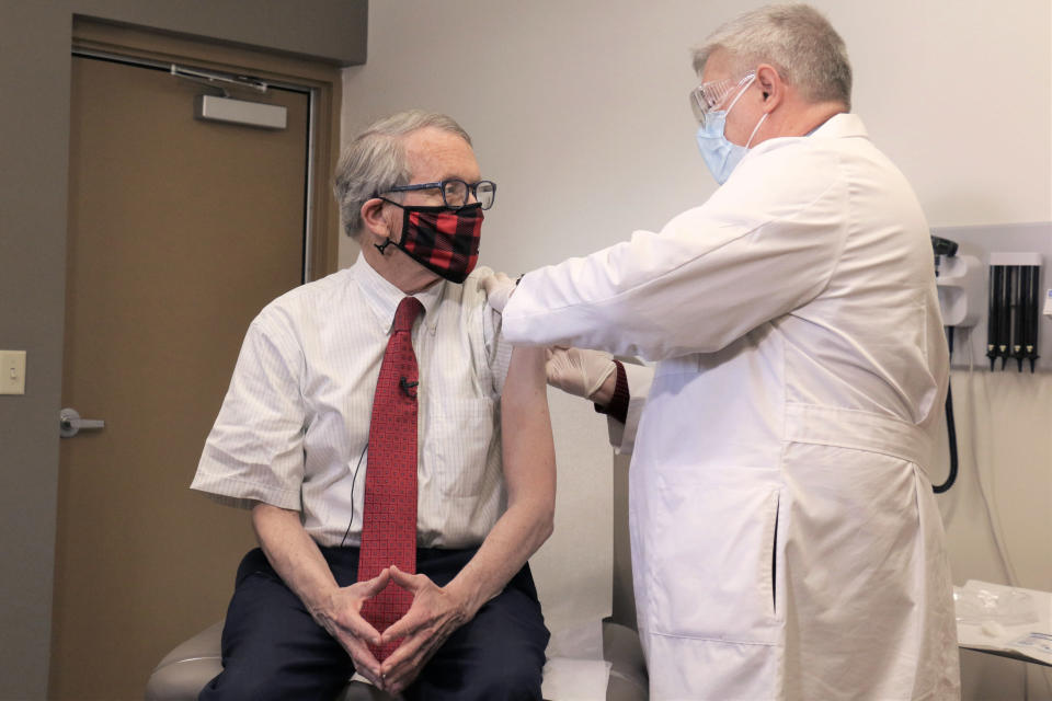 FILE - In this Tuesday, Feb. 2, 2021 photo provided by the Ohio Governor's Office, Gov. Mike DeWine, left, gets his first dose of the COVID-19 vaccine from Dr. Kevin Sharrett, in Jamestown, Ohio. On Friday, April 9, 2021, The Associated Press reported on stories circulating online incorrectly asserting masks are no longer mandatory in Ohio, and DeWine isn't saying a word about it. But masks remain mandatory in Ohio in indoor spaces as well as outdoors when social distancing is not possible. Ohio rescinded its previous coronavirus health orders on April 5, but the state issued a new order the same day simplifying the guidelines. (Ohio Governor's Office via AP)