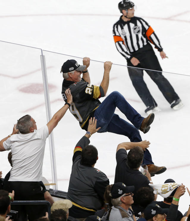 A fan tries to climb over the glass during the first period in Game 2 of the NHL hockey Stanley Cup Finals between the Vegas Golden Knights and the Washington Capitals on Wednesday, May 30, 2018, in Las Vegas. (AP Photo/Ross D. Franklin)
