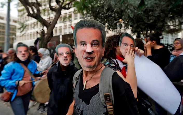 Lebanese anti-government protesters hold a mask of Lebanon's Central Bank Governor Riad Salameh