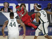 Texas Tech forward Tariq Owens (11) lands on the scorers table while trying to save a ball from going out of bounds in front of Michigan State's Nick Ward (44) and Cassius Winston (5) during the first half in the semifinals of the Final Four NCAA college basketball tournament, Saturday, April 6, 2019, in Minneapolis. (AP Photo/Matt York)