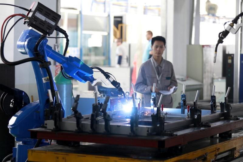 Worker monitors a robotic arm working inside a factory in Huaian