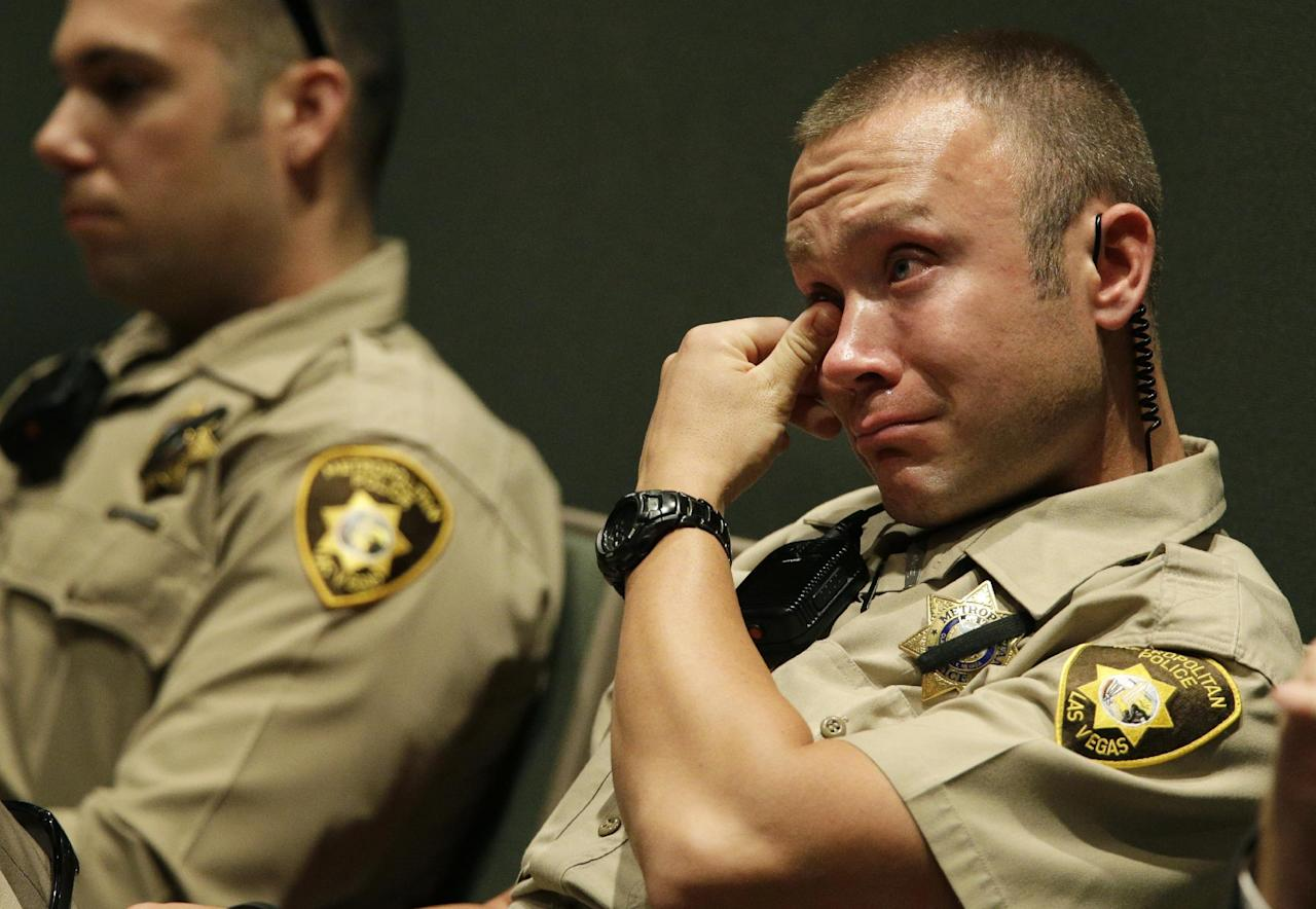 A Las Vegas Metropolitan Police officer cries during the funeral for Las Vegas Metropolitan Police Officer Igor Soldo at Canyon Ridge Christian Church Thursday, June 12, 2014 in Las Vegas. Two suspects shot and killed Soldo, 31, and fellow police officer Alyn Beck, 41, in an ambush at a Las Vegas restaurant Sunday, June 8, 2014, before fatally shooting a third person inside a nearby Wal-Mart, authorities said.(AP Photo/John Locher)