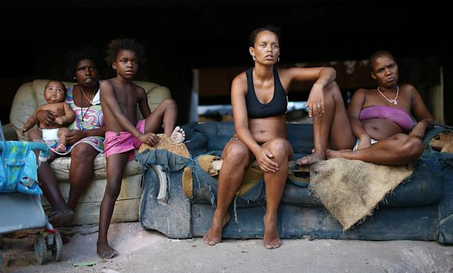 RIO DE JANEIRO, BRAZIL - MARCH 18: Residents (R-L) Luiza, Janubie, Leiticia, Anacleide and Lucas sit beneath an overpass near their houses in an impoverished area in the unpacified Complexo da Mare slum complex, one of the largest 'favela' complexes in Rio, on March 18, 2014 in Rio de Janeiro, Brazil. The group of 16 communities house around 130,000 residents while plagued by violence and poverty and dominated by drug gangs. Mare is located close to Rio's international airport and has been mentioned as a likely pacification target for the police. Rio's Police Pacification Unit (UPP) now controls 38 of the city favelas amid the city's efforts to improve security ahead of the 2014 FIFA World Cup and 2016 Olympic Games. (Photo by Mario Tama/Getty Images)