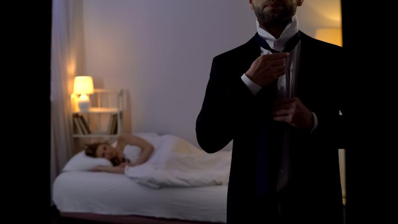Man putting business suit on and leaving sleeping mistress in bed, cheating