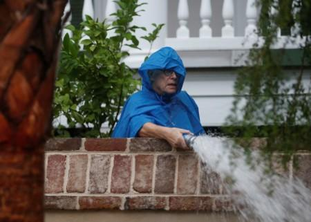 A resident pumps water from the yard of his home during Hurricane Dorian in Charleston