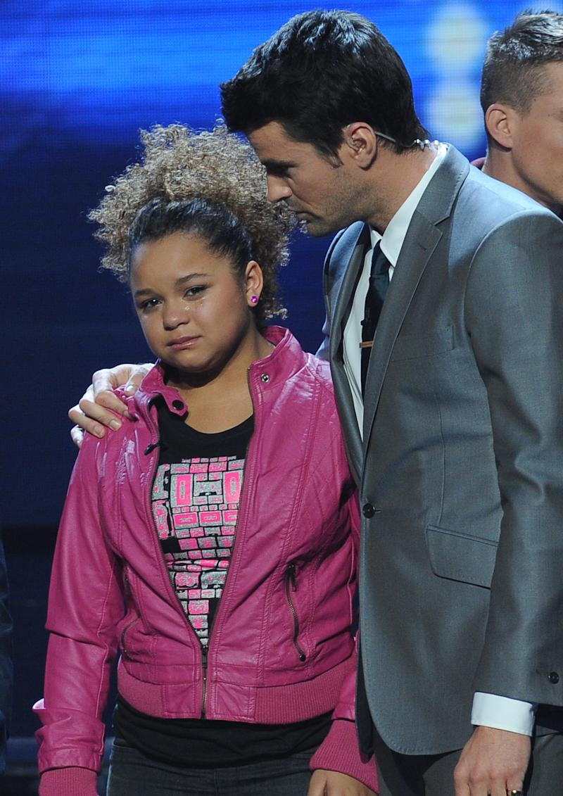 """In this Dec. 8, 2011 photo released by Fox, host Steve Jones, right, consoles contestant Rachel Crow after she was eliminated on the singing competition series """"The X Factor.""""  (AP Photo/Fox, Ray Mickshaw)"""