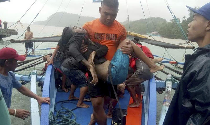 In this photo provided by the Philippine Coast Guard, coast guard rescuers carry a victim alive after being plucked from the waters off Guimaras Sunday, Aug. 4, 2019 in Iloilo province in central Philippines. Philippine police say rescuers have plucked more bodies in rough seas where three ferry boats capsized after being buffeted by fierce wind and waves off two central provinces.(Philippine Coast Guard Photo Via AP)
