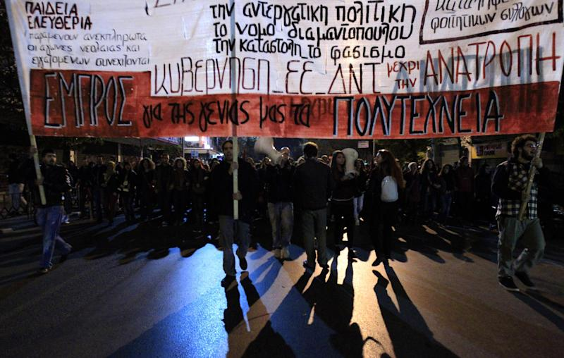 "Protesters march during a protest commemorating the student uprising against a military dictatorship in 1973, at the northern city of Thessaloniki Greece, Sat. Nov. 17 2012. The banner is reading ""Against Government - IMF - EU. In the northern Greek city of Thessaloniki, Greece's second-largest city, about 12,000 people marched, police said. Some burned a European Union flag, angry over EU demands to cut Greek spending in order to get a desperately needed bailout loan. (AP Photo/Nikolas Giakoumidis)"