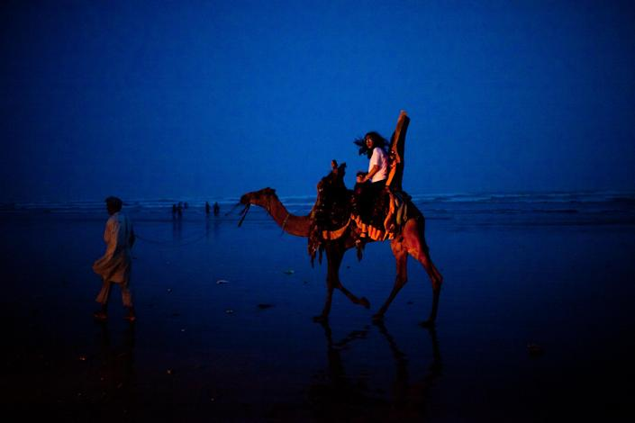 A woman takes a ride on a camel as people gather at Seaview waterfront to celebrate Pakistan's Independence Day on August 14, 2011 in Karachi, Pakistan. Pakistan celebrated it's 64th Independence day on August 14, the day before Pakistan was made an independent country based on border lines created by the British during the end of their rule of India. Pakistan became an independent country in 1947. (Photo by Daniel Berehulak/Getty Images)