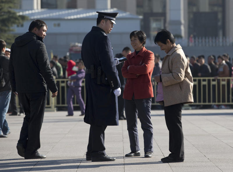 A policeman checks identities of women who visit Tiananmen Square in Beijing Thursday, Nov. 1, 2012 as the all-important Party Congress approaches. Beijing usually tightens security for high-profile political events, and this one is the most pivotal for the Communist Party in 10 years. But sometimes the measures can pass into the downright bizarre. (AP Photo/Andy Wong)