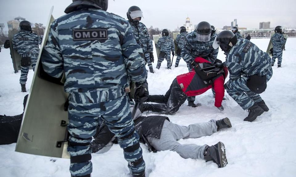 Police with riot shields and camouflage uniforms restrain two people lying down in the snow