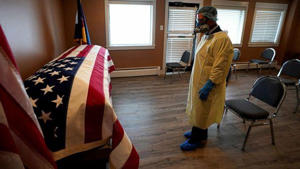 PHOTO: Michael Neel, funeral director of of All Veterans Funeral and Cremation, wearing full PPE, looks at the U.S. flag on the casket of George Trefren, a 90 year old Korean War veteran who died of COVID-19 in a nursing home, in Denver, April 23, 2020. (Rick Wilking/Reuters)