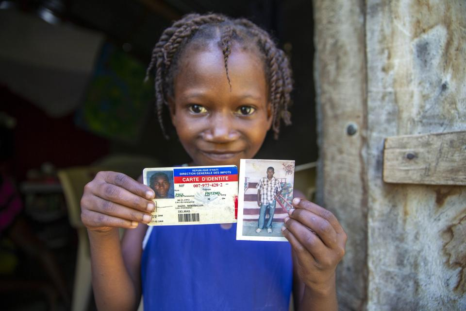 Eight-year-old Naffetalie Paul holds up an ID and photo of her late father Fritznel Paul, who died of cholera at age 39 when she was a newborn, as she stands in the doorway of her aunt's home where her father supported his two sisters and their six children in Mirebalais, Haiti, Monday, Oct. 19, 2020. Ten years after a cholera epidemic swept through Haiti and killed thousands, families of victims still struggle financially and await compensation from the United Nations as many continue to drink from and bathe in a river that became ground zero for the waterborne disease. (AP Photo/Dieu Nalio Chery)