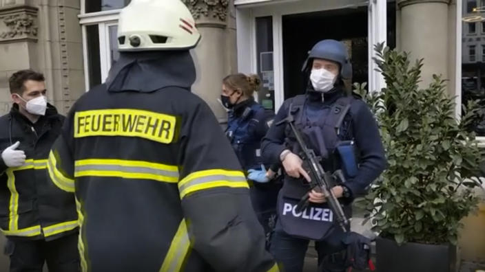 In this image from a video shows armed police officers and rescue workers speaking together near the scene of an incident in the city of Trier, Germany, Tuesday, Dec 1, 2020. German police say two people have been killed and several others injured in the southwestern German city of Trier when a car drove into a pedestrian zone. Trier police tweeted that the driver had been arrested and the vehicle impounded. (NonstopNews via AP)