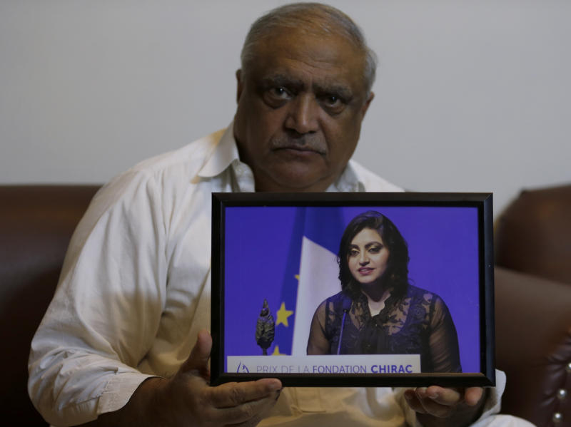 "Professor Mohammad Ismail, father of a Pakistani human rights activist Gulalai Ismail, holds a picture of his daughter as he poses for a photo, in his home in Islamabad, Pakistan, Thursday, Oct. 17, 2019. A dozen plainclothes Pakistani security forces attempted to raid the former home of Gulalai Ismaila who recently fled to the United States seeking asylum. Gulalai's elderly parents say they were ordered to come outside ""just to talk,"" but refused. Raids like the one early Thursday in the capital of Islamabad are part of an expanding push by Pakistan's security services to crack down on anyone who voices criticism of their activities. (AP Photo/Anjum Naveed)"