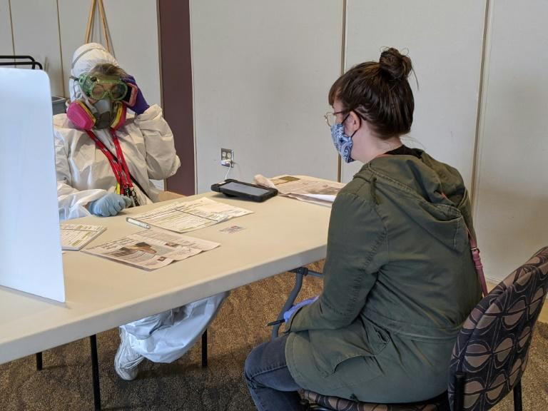 Elections Chief Inspector Mary Magdalen Moser (left) ran a polling station in Kenosha, Wisconsin, in hazmat gear as the US state conducted its primary election despite the coronavirus pandemic