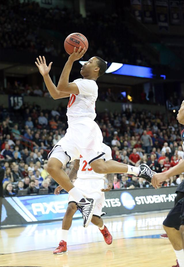 SPOKANE, WA - MARCH 20: Troy Caupain #10 of the Cincinnati Bearcats goes up against the Harvard Crimson during the second round of the 2014 NCAA Men's Basketball Tournament at Spokane Veterans Memorial Arena on March 20, 2014 in Spokane, Washington. (Photo by Stephen Dunn/Getty Images)