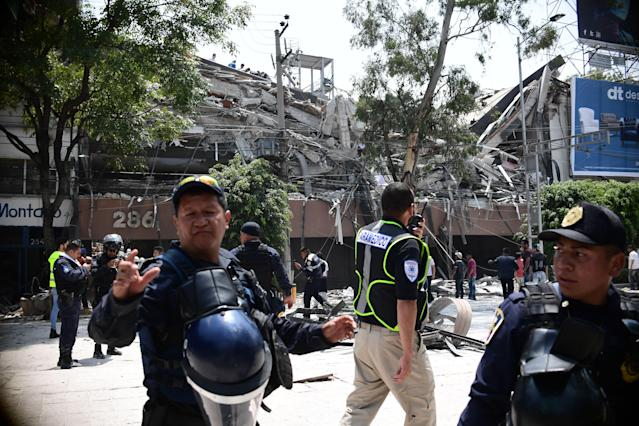 <p>Police officers cordon the area off after a building collapsed during a quake in Mexico City on September 19, 2017. A powerful earthquake shook Mexico City on Tuesday, causing panic among the megalopolis' 20 million inhabitants on the 32nd anniversary of a devastating 1985 quake. The US Geological Survey put the quake's magnitude at 7.1 while Mexico's Seismological Institute said it measured 6.8 on its scale. The institute said the quake's epicenter was seven kilometers west of Chiautla de Tapia, in the neighboring state of Puebla. (Photo: Ronaldo Schemidt/AFP/Getty Images) </p>