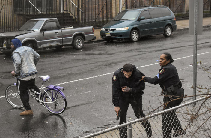 In this Dec. 10, 2019 photo, Jersey City police Sgt. Marjorie Jordan, right, helps fellow officer Raymond Sanchez to safety after he was shot during a gunfight that left multiple dead in Jersey City, N.J. The two killers were armed with a variety of weapons, including an AR-15-style rifle and a shotgun that they were wielding when they stormed into a store in an attack that left the scene littered with several hundred shell casings, broken glass and a community in mourning. Despite years of New Jersey officials focusing on the problems of crime guns coming into the state, Tuesday's shooting shows efforts are falling short. (Justin Moreau via AP)