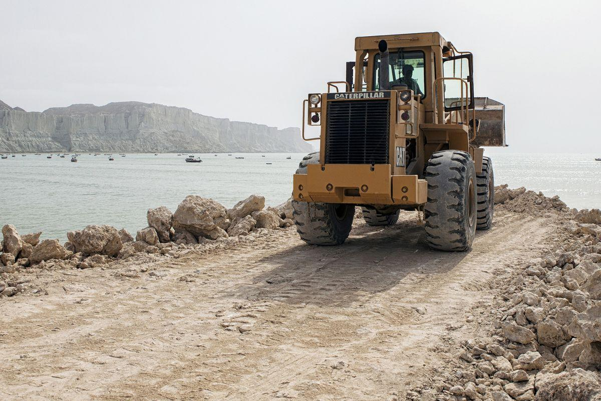 A bulldozer operates on a development site on Marine Drive in Gwadar, Balochistan, Pakistan, on Wednesday, Aug. 3, 2016. Gwadar is the cornerstone of Chinese President Xi Jinping's so-called One Belt, One Road project to rebuild the ancient Silk Road, a trading route connecting China to the Arabian Sea that slices through the Himalayas and crosses deserts and disputed territory to reach this ancient fishing port, about 500 miles by boat from Dubai. Photographer: Asim Hafeez/Bloomberg
