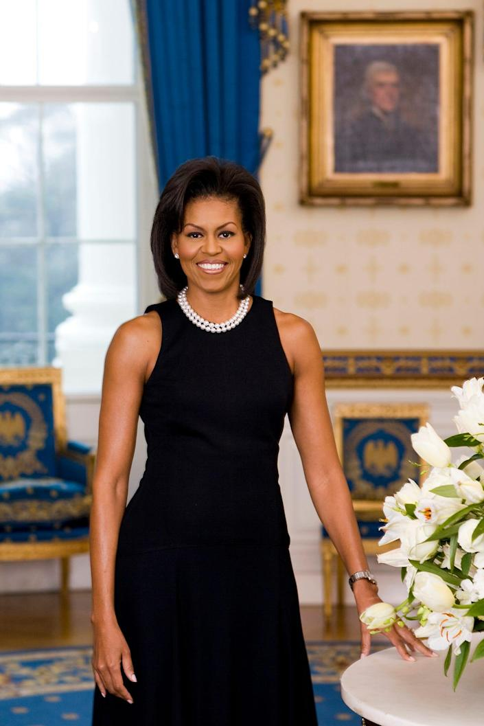In this handout image provided by the White House, first lady Michelle Obama poses for her official portrait in the Blue Room of the White House in February 2009 in Washington.